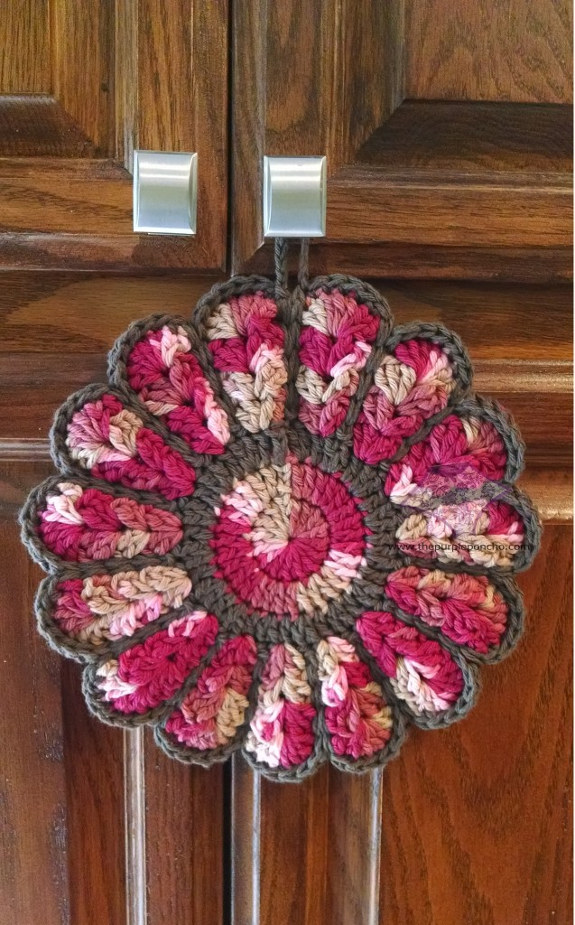 Flower potholder - variegated rose and pink colors with dark brown edging.